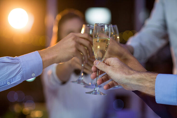 Group of businesspeople toasting glasses of champagne in office at night